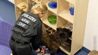 Polizistin mit einem neuen Polizei-Spürhund.