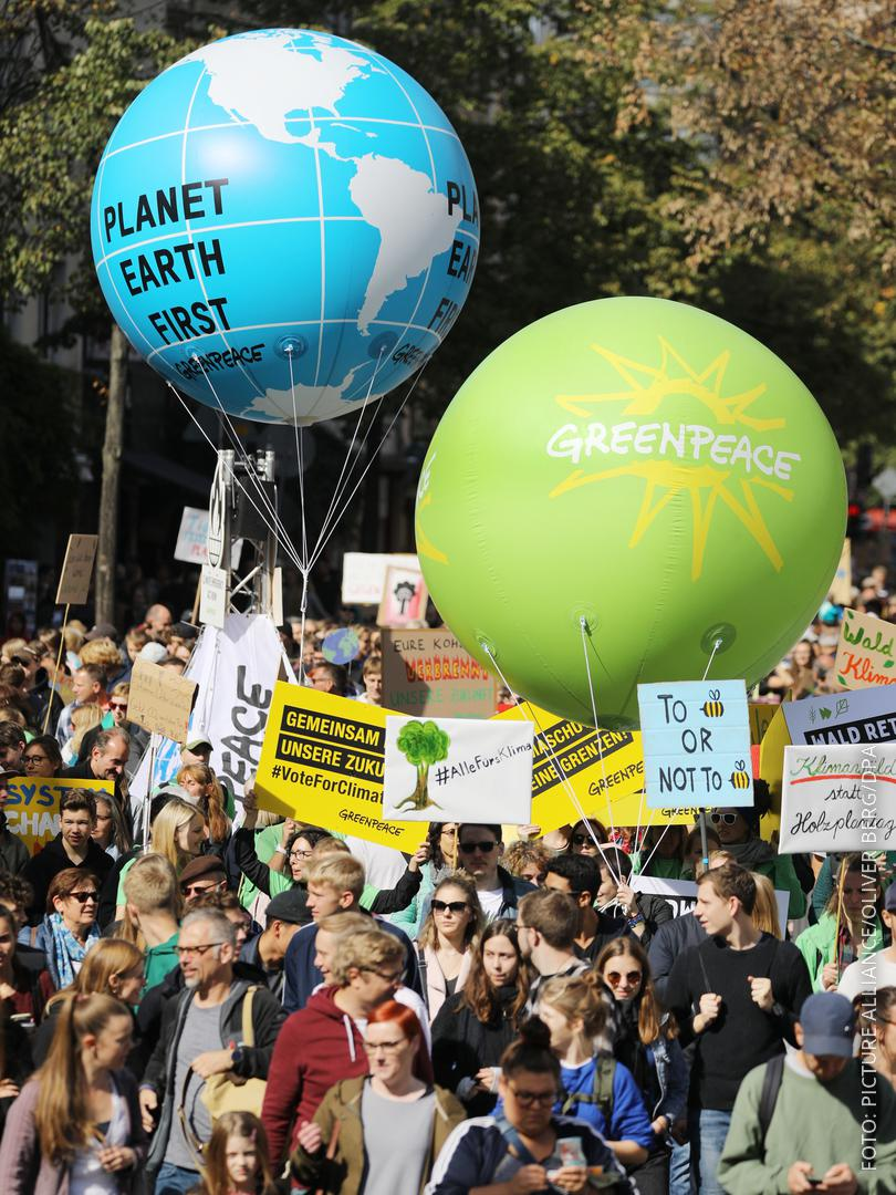 Teilnehmer einer Demonstration ziehen in Köln mit Transparenten und Ballons durch die Straßen