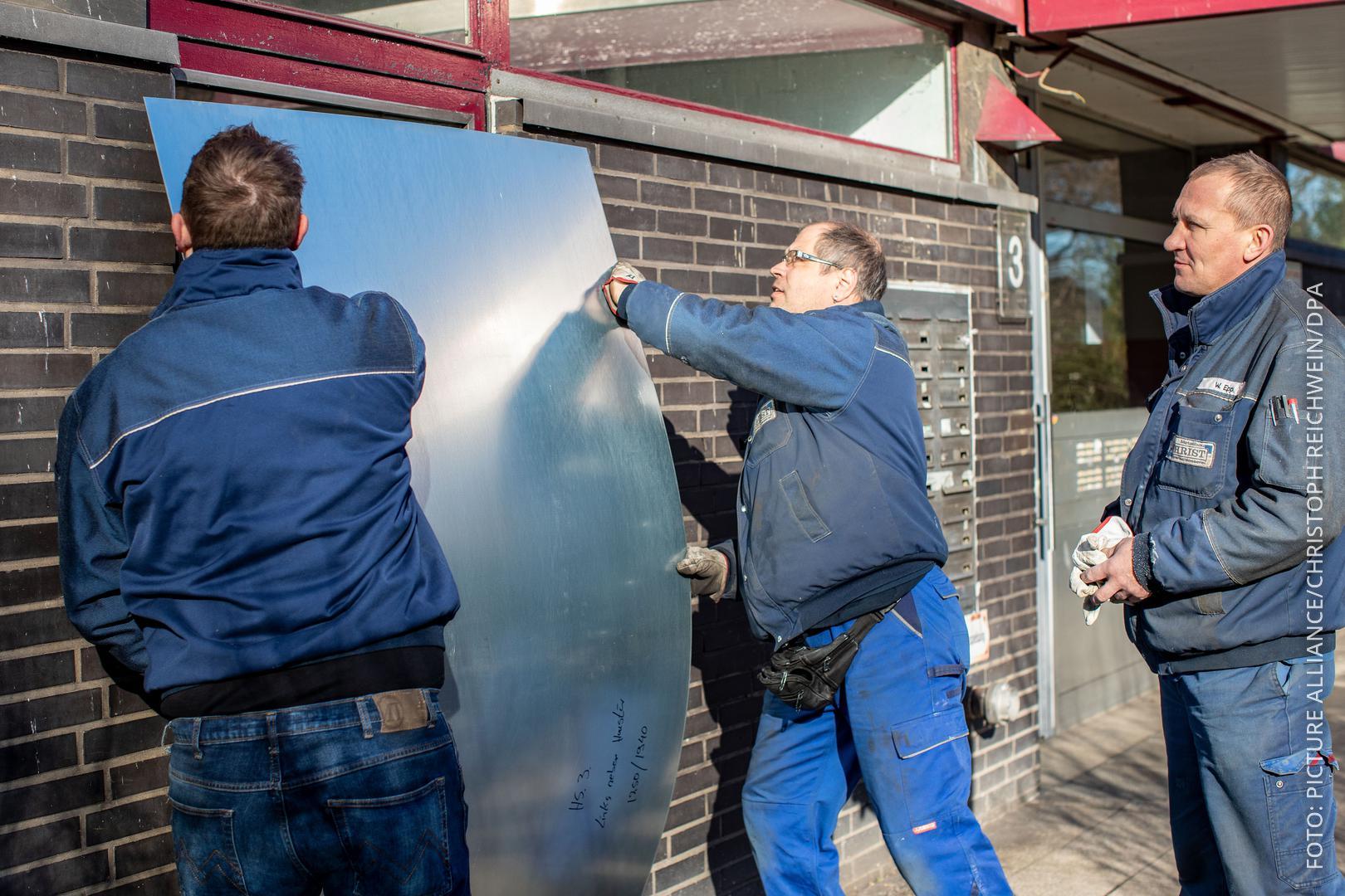Handwerker verschließen Kellerfenster
