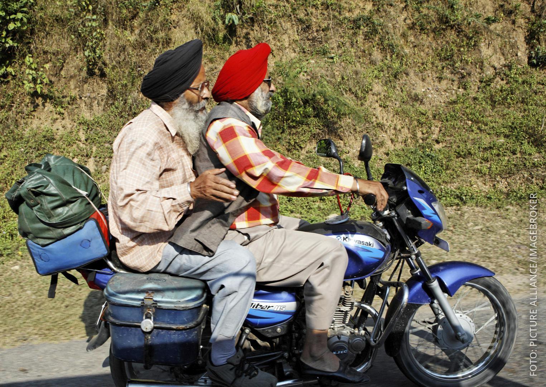Zwei Männer mit Turban fahren Motorrad