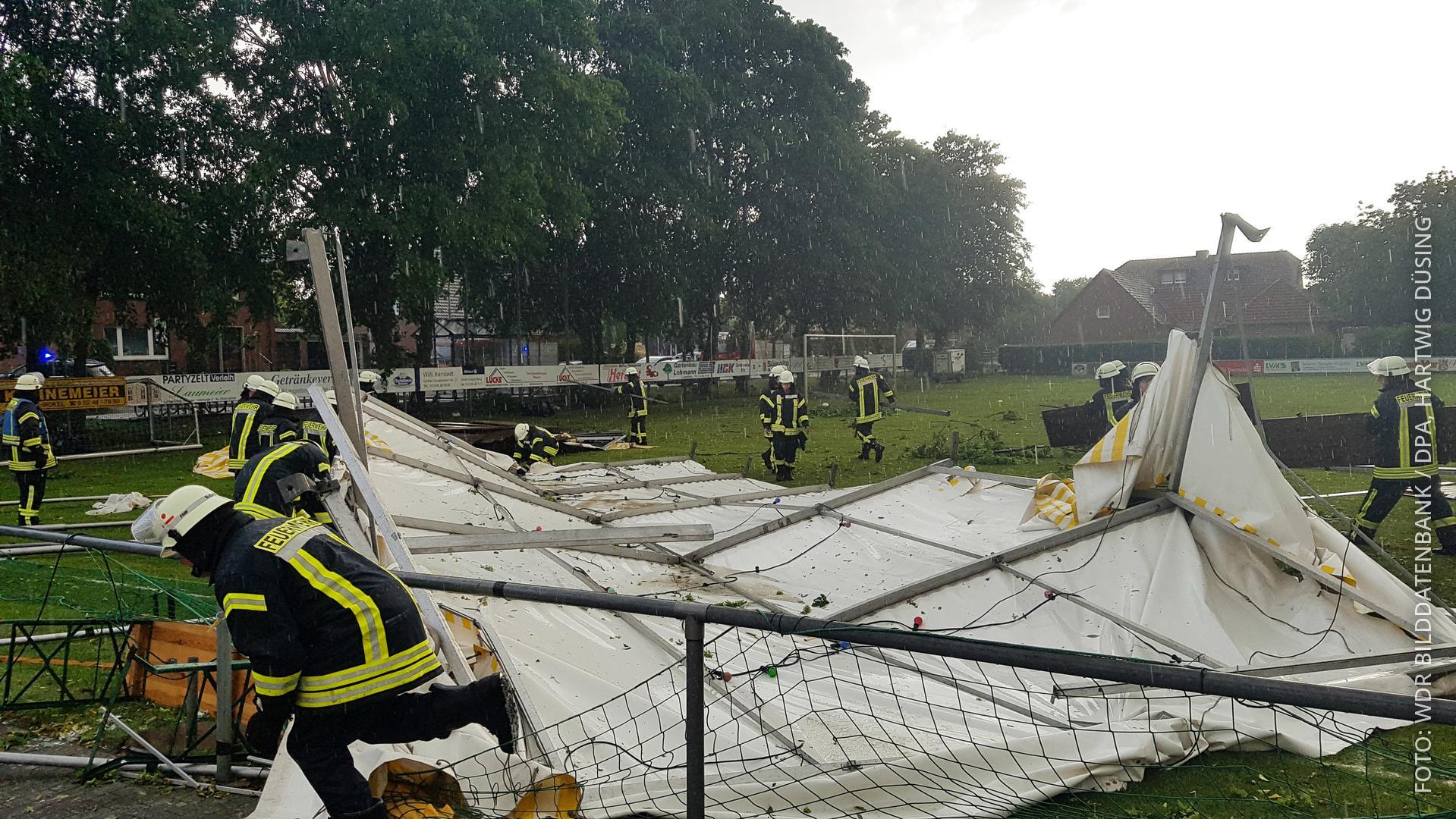 Feuerwehrleute stehen um kaputtes Partyzelt