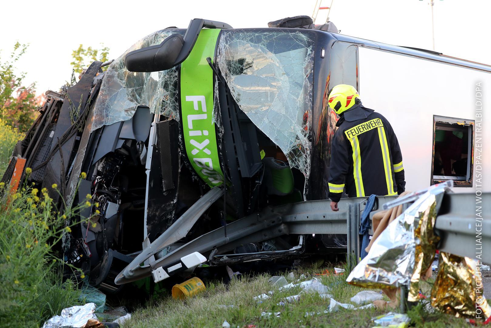 Der stark beschädigte Bus liegt auf der Seite und hat zum Teil die Leitplanke durchschlagen.
