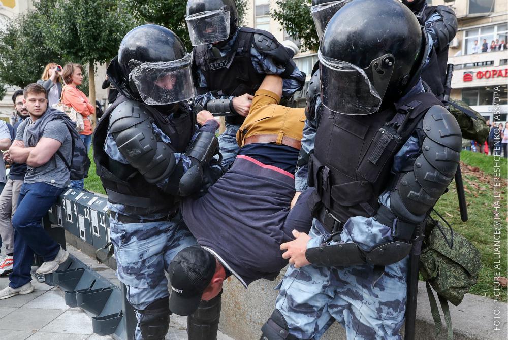 Polizisten in Moskau nehmen einen Demonstranten fest.