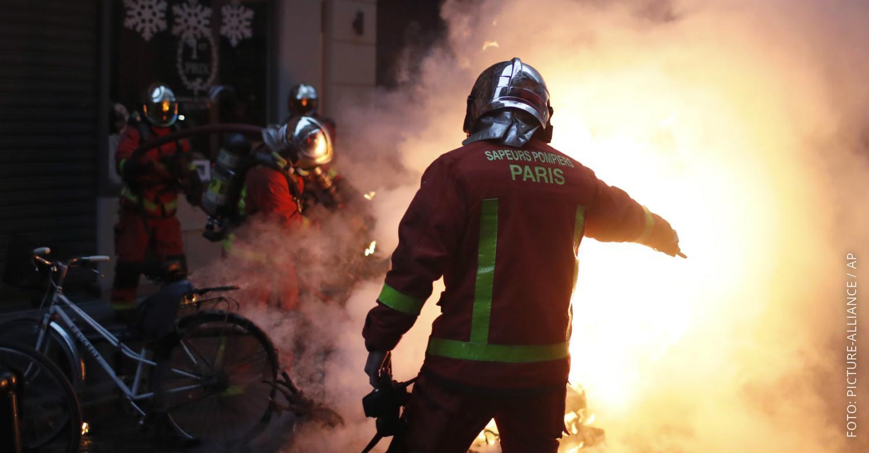 Feuerwehr-Männer in Paris löschen ein Feuer bei einer Demo.