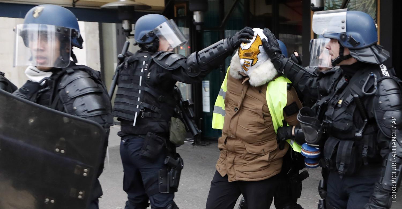 Französische Polizisten nehmen einen Demonstranten der Gelbwesten fest.