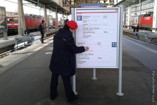 Bahn-Mitarbeiter schreibt Zug per Stift auf ein Board