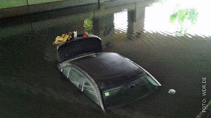 Schwarzes Auto, das bis zum Dach im Wasser steht.