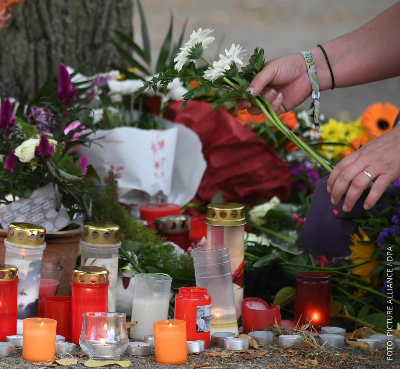 Eine Frau legt Blumen auf einem Spielplatz an der Stelle ab, an der ein 22-Jähriger gestorben ist.