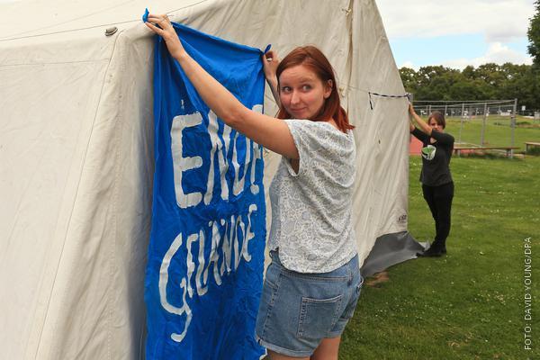 """Ein Frau befestigt an einem Zelt ein Banner """"Ende Gelände"""""""