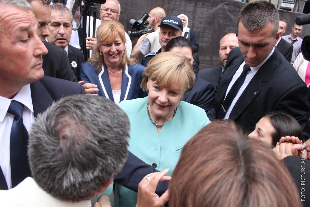 Kanzlerin Merkel wird bei einem Termin von Bodyguards geschützt.