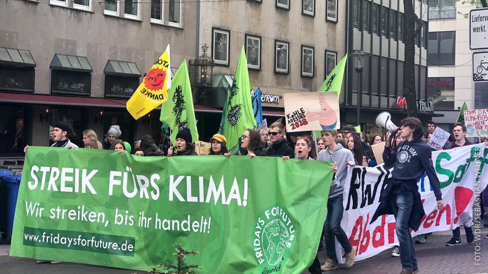 Demonstranten ziehen mit Plakaten durch die Essener Innenstadt