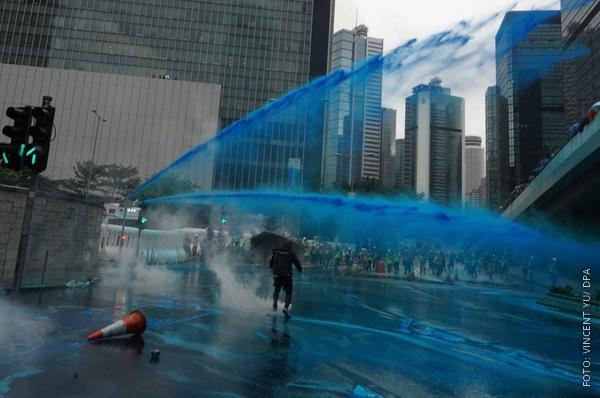 Wasserwerfer feuern blaues Wasser auf Demonstrierende in Hongkong