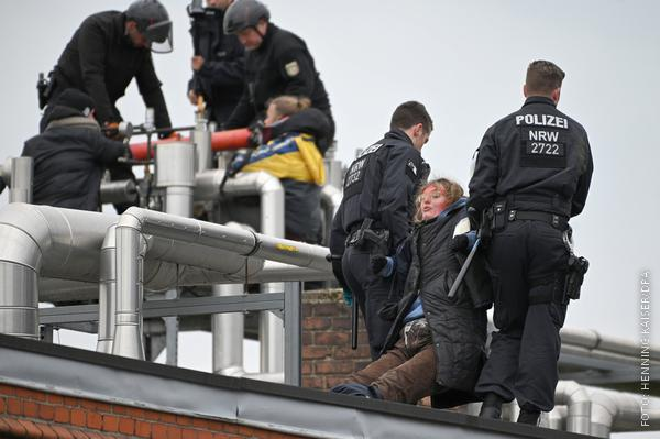 Aktivisten werden von Polizisten vom Dach gezogen